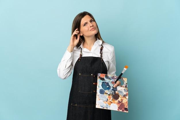 Молодой художник словацкая женщина изолирована на синей стене, сомневаясь