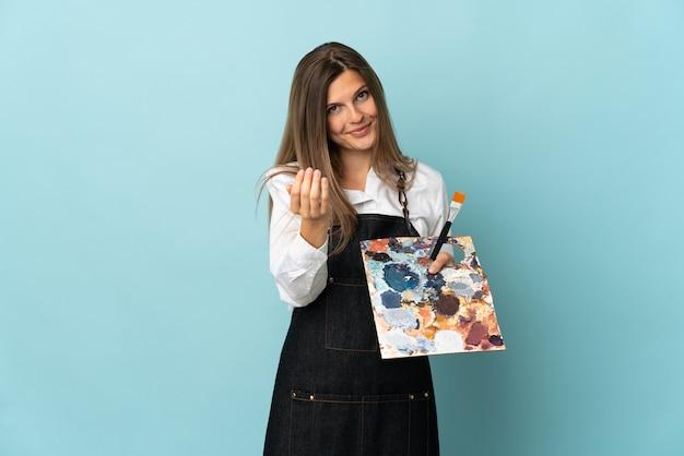 젊은 예술가 슬로바키아어 여자 손으로 올 초대 파란색 벽에 격리. 와줘서 행복해