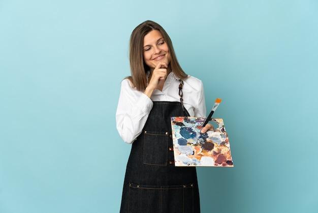 Молодой художник словацкая женщина изолирована на синей стене, глядя в сторону и улыбаясь