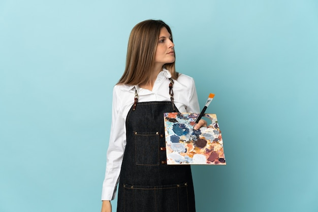 Молодой художник словацкая женщина изолирована на синей стене, глядя в сторону