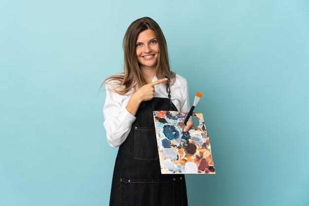 Молодой художник словацкая женщина изолирована на синей стене, указывая в сторону, чтобы представить продукт