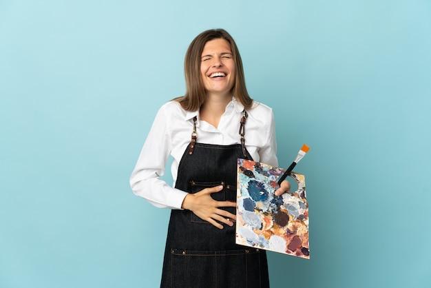 Молодой художник словацкая женщина изолирована на синей стене, много улыбаясь