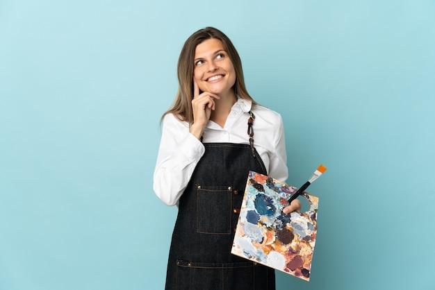 Молодой художник словацкая женщина изолирована на синей стене, думая об идее, глядя вверх