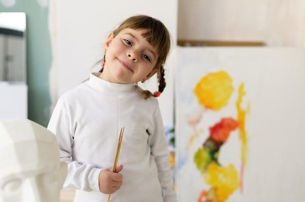 若いアーティストが自宅のスタジオ ワークショップに立ち、アート ブラシを持ち、楽しそうに微笑む