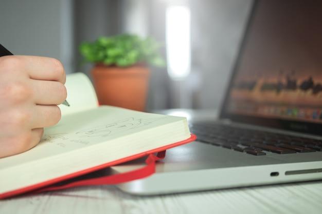 Молодая художница женщина рисует в своей записной книжке с помощью карандаша, творческого карандашного искусства, художественного творческого рабочего пространства фоновой фотографии