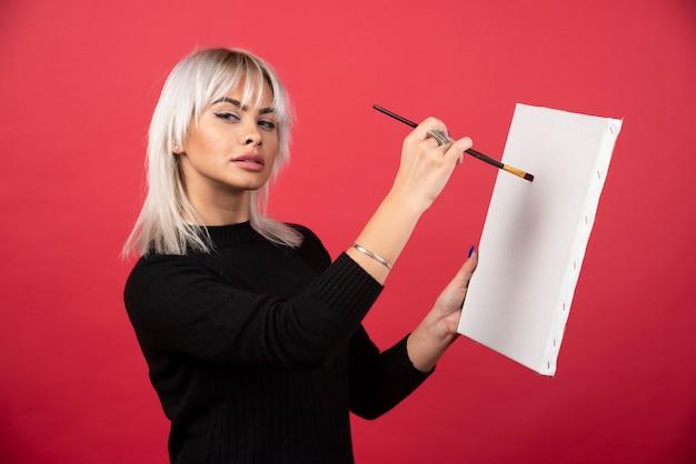 赤い壁にキャンバスに描く若い芸術家の女性。