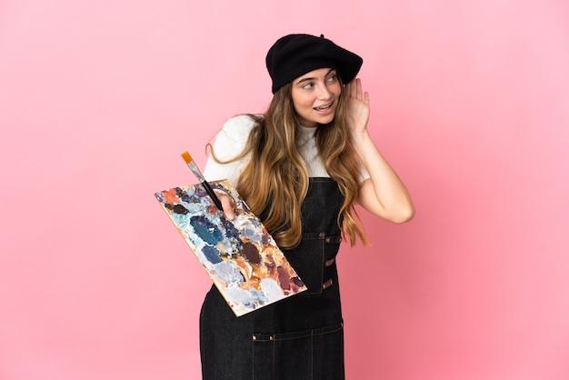 耳に手を置いて何かを聞いてピンクで分離されたパレットを保持している若いアーティストの女性