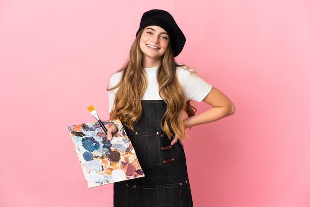 Молодая художница, держащая палитру изолирована на розовом, позирует с руками на бедрах и улыбается