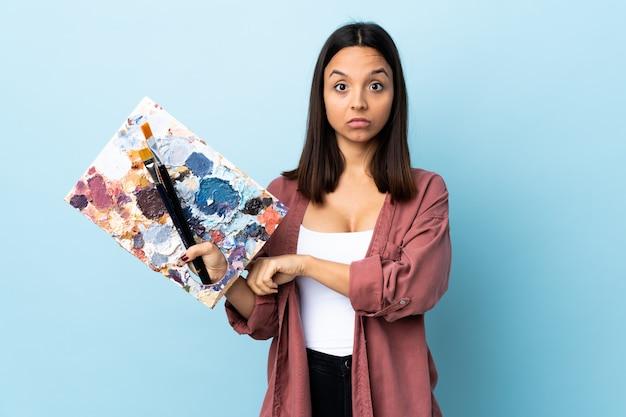 Молодой художник женщина держит палитру над синей стеной, делая жест опоздания