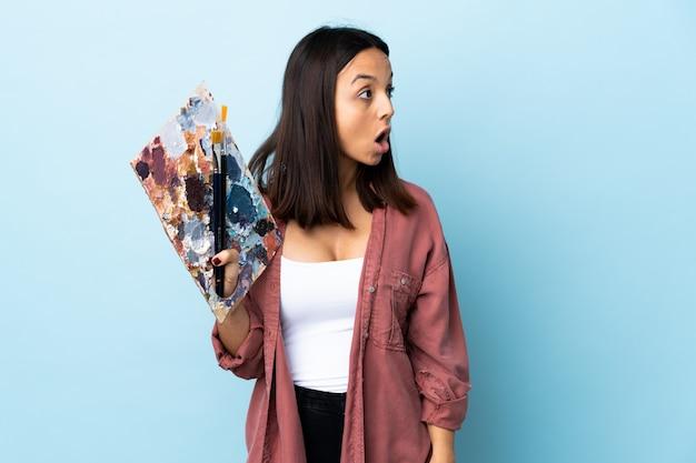 若いアーティストの女性が側に見ながら驚きのジェスチャーを行う孤立した青い背景の上にパレットを置く