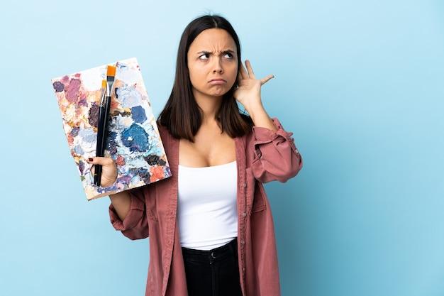 耳に手を置くことによって何かを聞いて孤立した青い背景の上にパレットを保持している若いアーティストの女性。