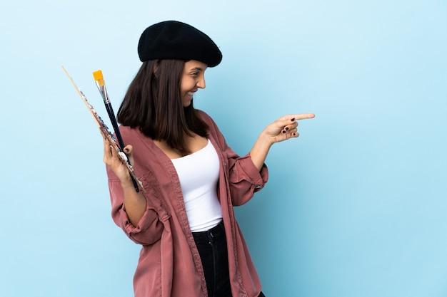 Молодая женщина-художник, держащая палитру на изолированном синем фоне, указывая пальцем в сторону и представляя продукт.