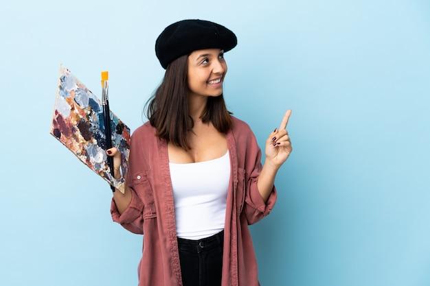 素晴らしいアイデアを指している孤立した青い背景の上にパレットを置く若いアーティスト女性