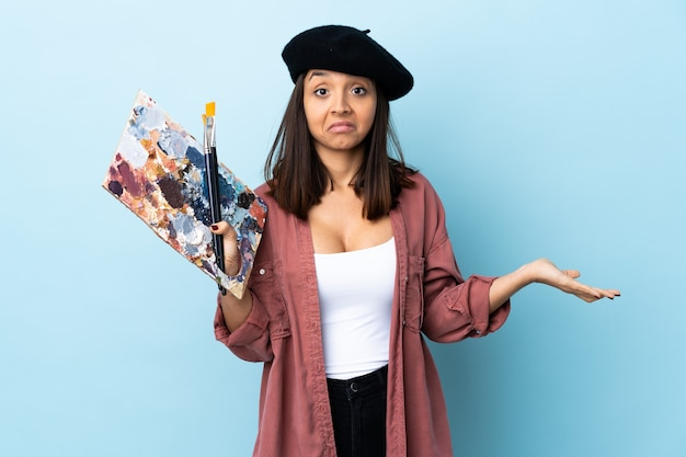 격리 된 파란색 배경 위에 팔레트를 들고 젊은 예술가 여자