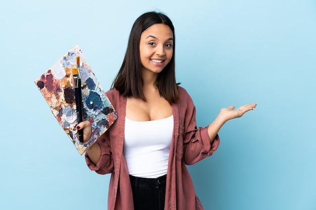 Молодой художник женщина, держащая палитру над изолированной синей стеной, представляя идею, глядя на нее.