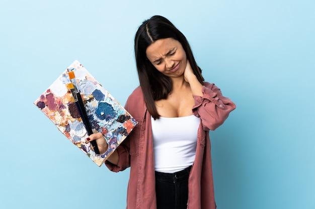 首痛で孤立した青い壁にパレットを保持している若いアーティスト女性