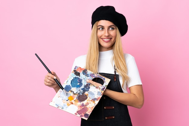 Молодой художник женщина держит палитру над изолированной розового пространства