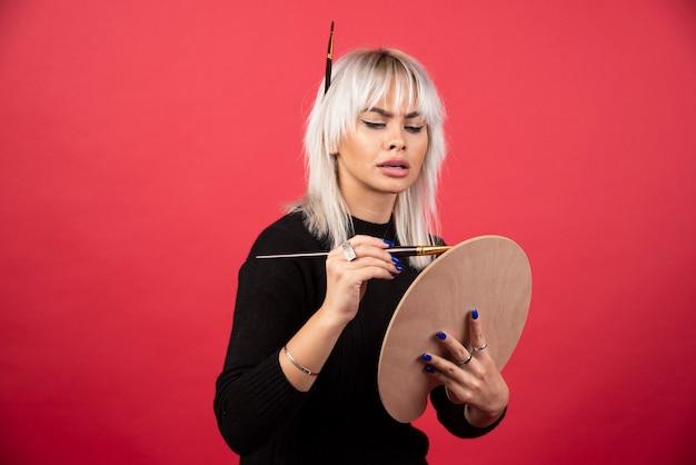 Молодая женщина художника, держащая художественные принадлежности на красной стене.
