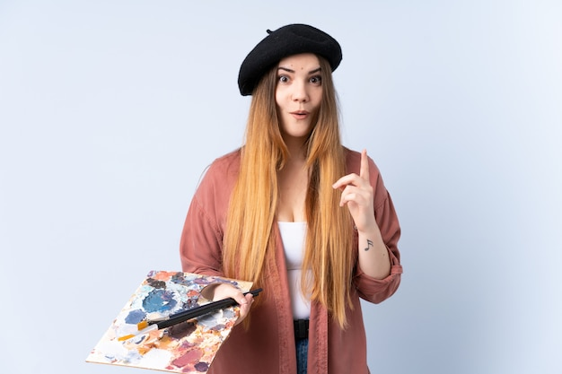 Young artist woman holding a palette on blue wall with surprise facial expression