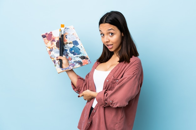 Young artist woman holding a palette over isolated blue extending hands to the side for inviting to come