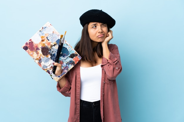 Young artist woman holding a palette over isolated blue wall frustrated and covering ears