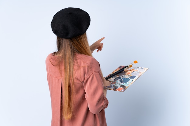 Young artist woman holding a palette isolated on blue wall pointing back with the index finger