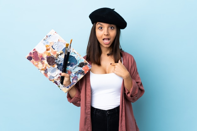 Young artist woman holding a palette over isolated blue wall with surprise facial expression