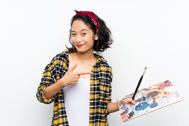 Young artist woman holding a palette over isolated white background and pointing it