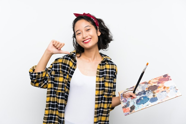 Young artist woman holding a palette over isolated white background proud and self-satisfied