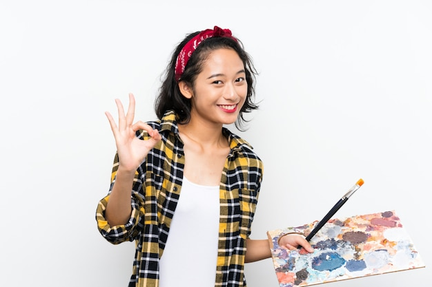 Young artist woman holding a palette over isolated white background showing ok sign with fingers