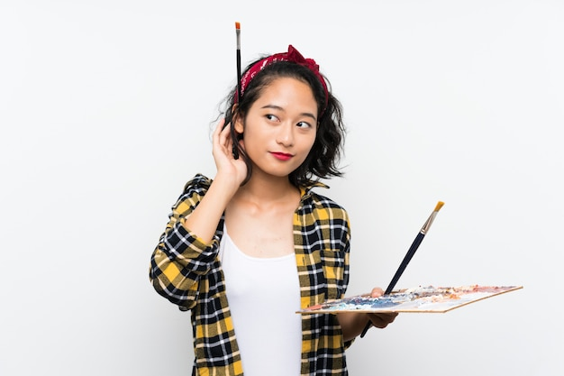 Young artist woman holding a palette over isolated white background