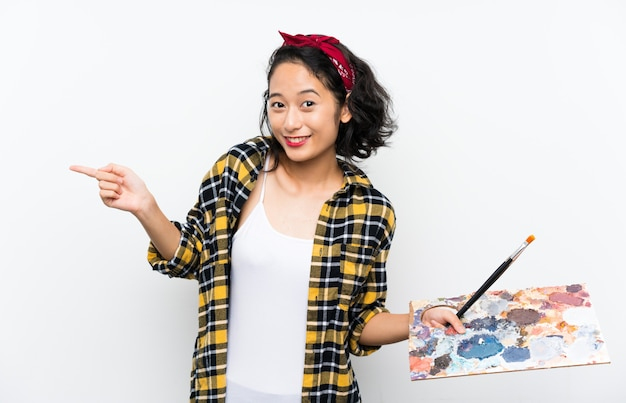 Young artist woman holding a palette over isolated white wall surprised and pointing finger to the side