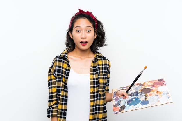 Young artist woman holding a palette over isolated white wall with surprise and shocked facial expression
