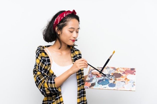 Young artist woman holding a palette over isolated white wall