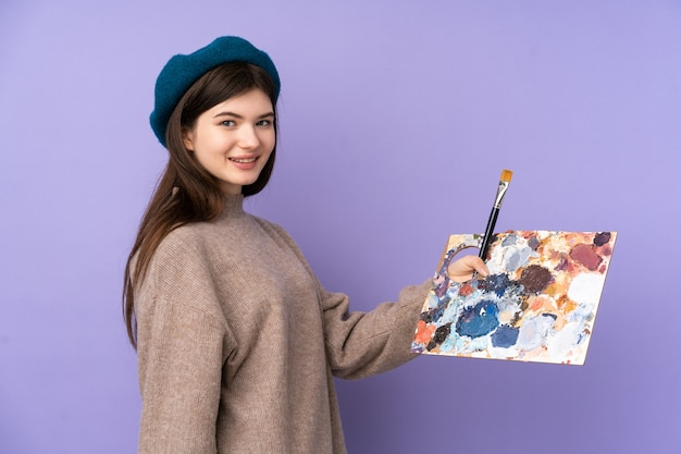 Young artist woman holding a palette with happy expression