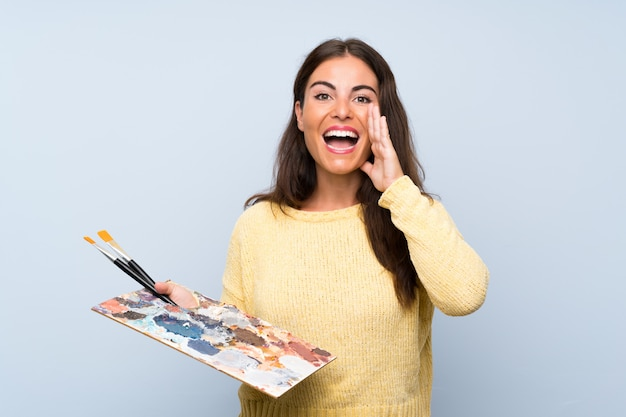 Young artist woman over isolated blue wall shouting with mouth wide open