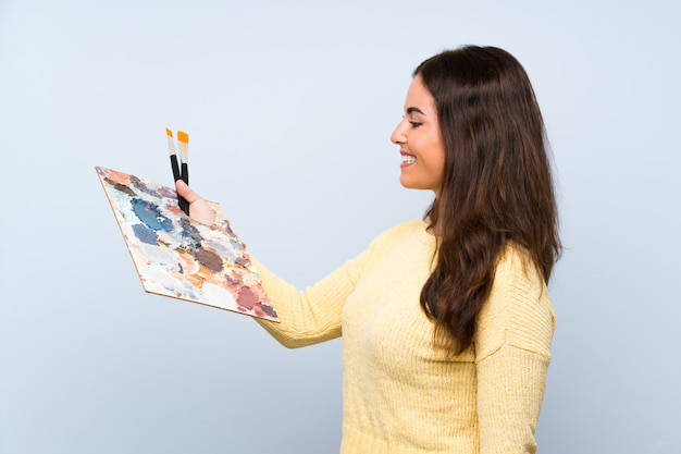 Young artist woman over isolated blue wall with happy expression