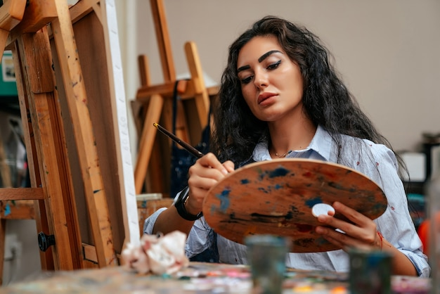Young artist working on a painting at the studio