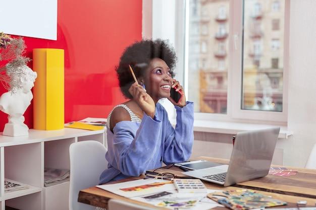 젊은 예술가. 그녀의 사무실에 앉아 약간의 영감을 가지고 연필을 들고 젊은 유망한 예술가
