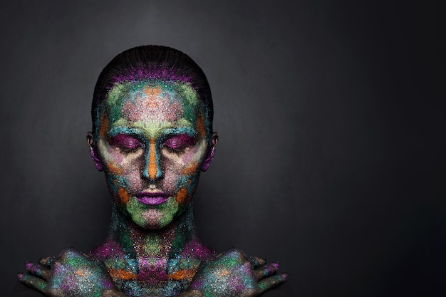 Young artistic woman in black paint and colourful powder. glowing dark makeup. creative body art on the theme of space and stars. bodypainting project: art, beauty, fashion.