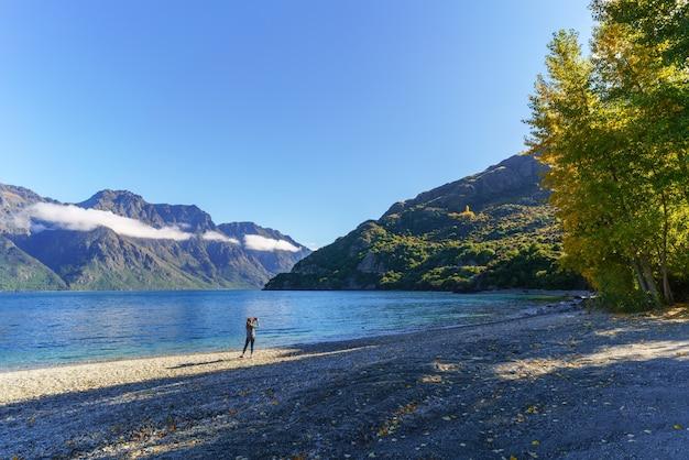 ニュージーランドの南島、美しいワカティプ湖の写真を撮る若いアサインの女性
