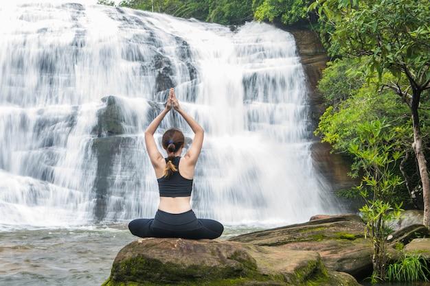 Молодые женщины asain практикуя йогу перед грандиозным водопадом.