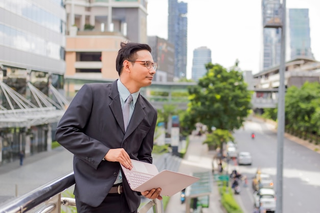 Young asia businessman in suit with his laptop computer outdoors, modern building on the background