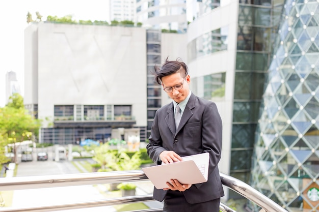 Young asia businessman in suit with his laptop computer outdoors