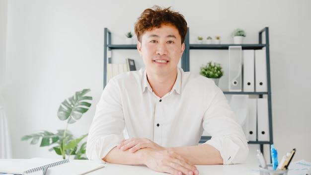 Il giovane uomo d'affari asiatico che utilizza un computer portatile parla con i colleghi del piano in una riunione di videochiamata mentre lavora da casa in soggiorno.