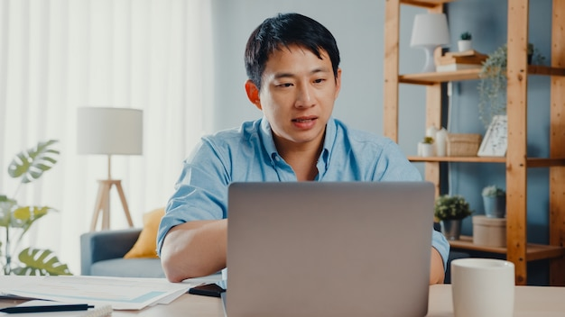 Young asia businessman using laptop talk to colleagues about plan in video call while smart working from home