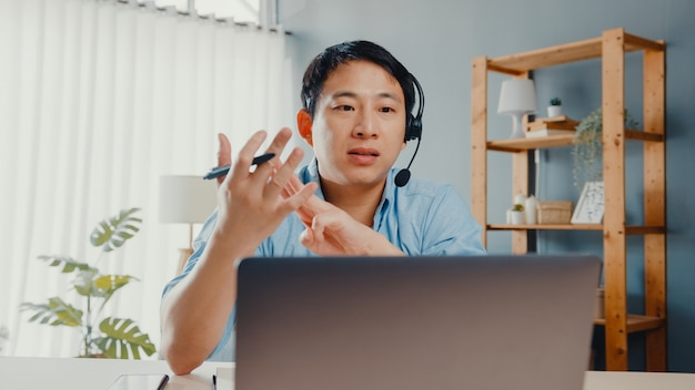 Young asia businessman wear headphones using laptop talk to colleagues about plan in video call while work from home at living room.