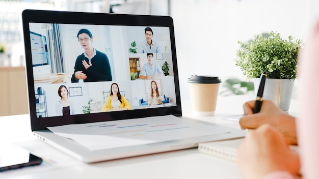 Young asia businesswoman using laptop talk to colleague about plan in video call meeting while work from home at living room.