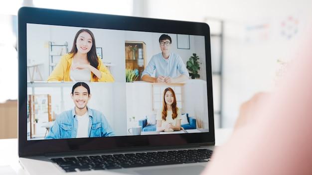 Молодой азиатский бизнесвумен с помощью ноутбука поговорить с коллегой о плане видеозвонка во время работы из дома в гостиной.