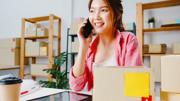 Young asia businesswoman using mobile phone call receiving purchase order and check product on stock, work at home office. small business owner, online market delivery, lifestyle freelance concept.